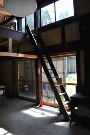 屋根裏への梯子。右に薪ストーブ